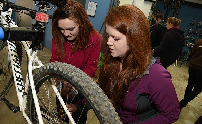 Student servicing a mountain bike