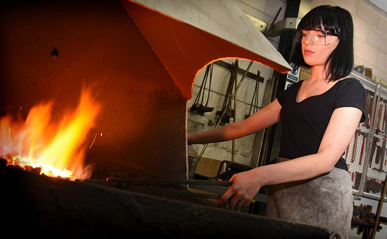 Student heating a piece of metal in the hot coals